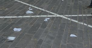 People feet walking in the street with paper litter. TEL AVIV, ISRAEL- MARCH 10, 2017: People walking in the paved street, wind blowing up paper litter and dry stock footage