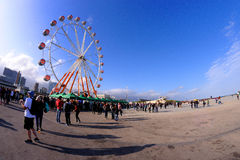 People and a ferris wheel at a Festival. Royalty Free Stock Photography