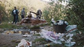 People filling bottles from rusty pipe waterspring in woods full of trash. Refugee concept, society or ecology problems stock video footage