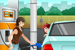 People filling up gasoline at the gas station. A vector illustration of a young woman  filling up gasoline at the gas station Royalty Free Stock Images