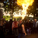 People with fire as a zombie parades on a street during a zombie walk in Paris. Stock Images