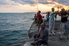 People fish in Black sea from landing stage Stock Photo