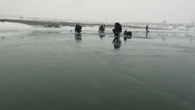 People fishermen go sit on competition on ice in winter stock video footage