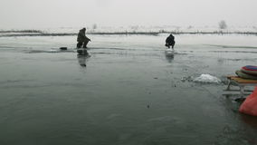 People fishermen go sit on competition on ice in winter stock video