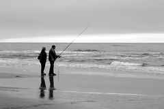 People fishing on beach. Couple fishing from sandy beach under gray sky stock images