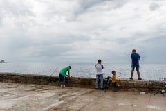 HAVANA, CUBA - OCTOBER 21, 2017: People Fishing in Havana, Cuba. Malecon Avenue. People Fishing in Havana, Cuba. Malecon Avenue Royalty Free Stock Images