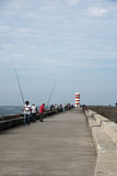 People fishing infront of lighthouse Royalty Free Stock Image