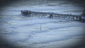 People on fishing pier watching the waves and wind blow. Waves rolling under fishing pier Daytona Beach, Florida - Travel and leisure concept stock video footage