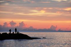 People are fishing on the rocks near the sea at sunset. Peole are fishing on the rocks near the ocean at sunset Stock Photos