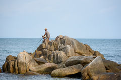 People fishing on a rocky beach Royalty Free Stock Photography