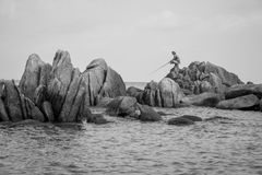 People fishing on a rocky beach Royalty Free Stock Photo