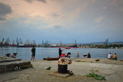 People fishing at seaport. People fishing peacefully at Varna seaport pier against dramatic cloudy sky Stock Images