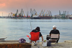 People fishing at seaport Stock Photo