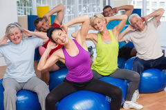 People on fitness balls exercising in gym class. Happy fit people on fitness balls exercising in gym class Royalty Free Stock Photo