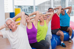 People on fitness balls exercising in gym class. Portrait of happy people on fitness balls exercising in gym class Royalty Free Stock Photos