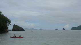 People floating in a kayak on the background island with rocks in the azure sea. Near the beach in cloudy weather stock video
