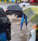 People in flooded rainy city. Women crossing flooded urban road in the heavy rain stock image