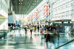 People flow through the concourse of the Javitz Center. Slowed shutter image shot in the concourse of the Javitz Center in New York City, to create the Stock Photography