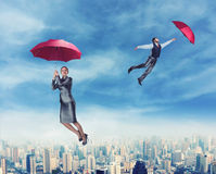 People flying in the sky with umbrellas Stock Images