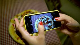 People and food concept. Young woman in a restaurant make photo of food with mobile phone camera