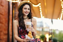 People, food, rest and lifestyle concept. Brunette woman with long hair, wearing summer dress and hat, drinking takeaway coffee an. D eatting croissant while stock image