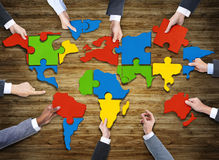 People Forming World Map with Puzzle Pieces Royalty Free Stock Photo