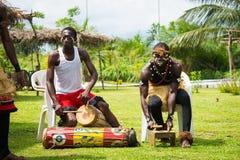 People in FRANCEVILLE, GABON. FRANCEVILLE, GABON - MARCH 6, 2013: Unidentified Gabonese men in paint prepare drum for dancing abilities in Gabon, Mar 6, 2013 Royalty Free Stock Image
