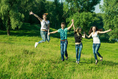 People, freedom, happiness, and teenage concept. group of happy friends wearing sunglasses jumping high grass background Stock Images
