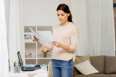 Woman with papers working or learning at home. People, freelance and education concept - woman with papers and laptop working or learning at home Royalty Free Stock Photography