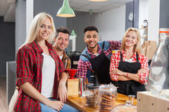 People friends drinking coffee shop talking laughing with barista sitting at bar counter Stock Photo
