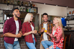 People Friends Drinking Orange Juice Talking Laughing Sitting At Bar Counter, Mix Race Man And Woman Couple Royalty Free Stock Image