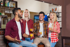 People Friends Drinking Orange Juice Talking Laughing Sitting At Bar Counter, Mix Race Man And Woman Couple Royalty Free Stock Images