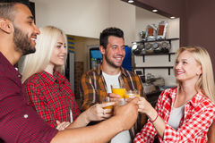 People Friends Drinking Orange Juice, Toasting At Bar Counter, Mix Race Man And Woman Cheers Stock Photography