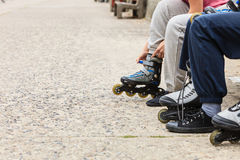 People friends putting on roller skates outdoor. Royalty Free Stock Photo