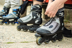 People friends putting on roller skates outdoor. Royalty Free Stock Photos