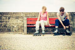 People friends putting on roller skates outdoor. Stock Image