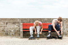 People friends putting on roller skates outdoor. Royalty Free Stock Images
