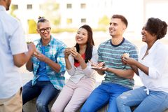 Friends eating pizza and sandwiches in park royalty free stock photography
