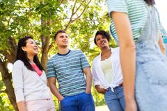 Happy international friends talking in park royalty free stock images