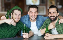 Happy male friends drinking beer at bar or pub. People, friendship and st patricks day concept - happy male friends drinking bottled beer and hugging at bar or stock photo