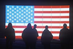 People in front of an American Flag. Silhouettes of People in front of an American electric Flag, Winter Olympics, Salt Lake City, Utah Stock Photos