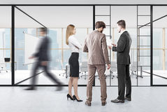 People in front of a meeting room. With glass walls and panoramic windows. There is a whiteboard and a long desk in it. 3d rendering Royalty Free Stock Images