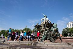 People in front of the Neptune fountain - Neptunbrunnen with Greek god Poseidon and woman statues in Berlin, Germany. BERLIN, GERMANY - MAY 15 2018: People in Stock Photography