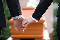 People at funeral consoling each other. Religion, death and dolor - couple at funeral holding hands consoling each other in view of the loss Stock Image