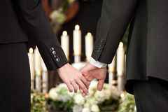 People at funeral consoling each other. Religion, death and dolor  - couple at funeral holding hands consoling each other in view of the loss Royalty Free Stock Photos