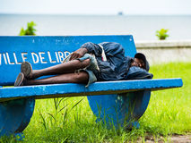 People in GABON. GABON - MARCH 6, 2013: Unidentified Gabonese homeless man in shorts sleeps on a bench in Gabon, Mar 6, 2013. People of Gabon suffer of poverty Stock Photos