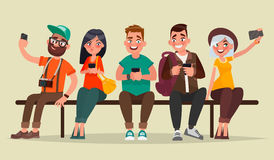 People and gadgets. Group of students sitting on a bench enjoyin Stock Photo