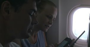 People with Gadgets on a Plane. Man and woman are sitting by in a plane, woman is writing in tablet, man is using smartphone stock footage