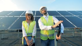 People with gadgets stand on solar panels background, close up.