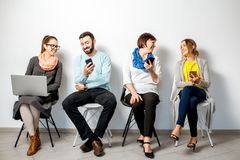 People with gadgets on the white background. People in colorful casual clothes using gadgets sitting in a row on the white wall background Royalty Free Stock Photography